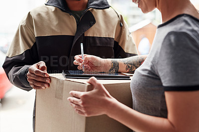 Buy stock photo Cropped shot of an unrecognizable woman using a digital tablet to sign for her delivery from a male courier at her home