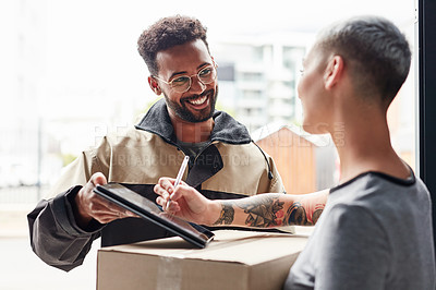 Buy stock photo Cropped shot of a handsome young male courier helping a female customer sign for her home delivery on a digital tablet