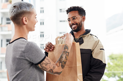 Buy stock photo Cropped shot of a handsome young male courier smiling while making a home delivery to a female customer during the day