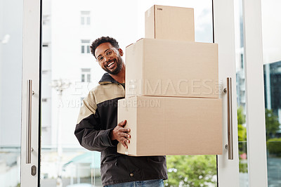 Buy stock photo Cropped shot of a handsome young male courier holding a load of boxes while making a home delivery during the day