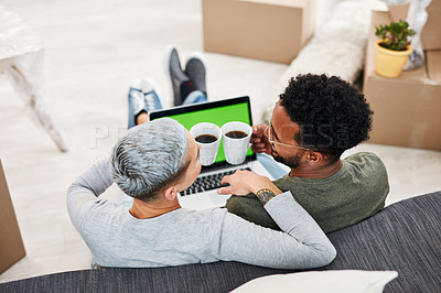 Buy stock photo Rearview shot of a couple using a laptop while sitting in their new home