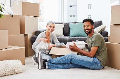 Buy stock photo Shot of a young couple unpacking boxes in their new home