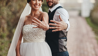 Buy stock photo Cropped shot of a young couple showing of their rings on their wedding day