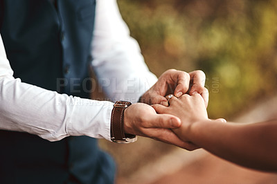 Buy stock photo Cropped shot of an unrecognizable man putting a ring on his wife's finger