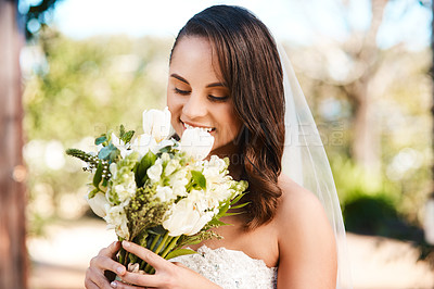 Buy stock photo Cropped shot of a beautiful young bride smiling while holding a bouquet of flowers on her wedding day