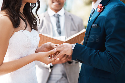 Buy stock photo Cropped shot of an unrecognizable bride slipping a ring on to her groom's finger while standing at the altar on their wedding day