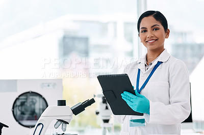 Buy stock photo Cropped portrait of an attractive young female scientist smiling while holding a digital tablet in a laboratory