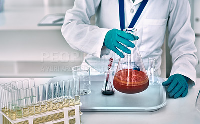 Buy stock photo Cropped shot of an unrecognizable female scientist conducting an experiment with a red liquid in a laboratory