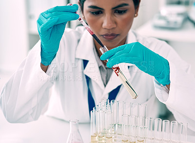 Buy stock photo Cropped shot of an attractive young female scientist transferring a blood sample from a pipette to a test tube in a laboratory