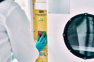 Buy stock photo Cropped shot of an unrecognizable female scientist operating an incubator while working in a laboratory