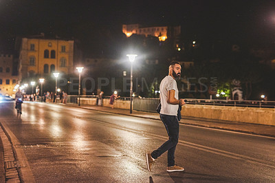 Buy stock photo Full length shot of a handsome young man walking across the street while sightseeing in Italy at night