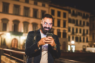 Buy stock photo Cropped shot of a handsome young man standing on a bridge and using his cellphone while touring Italy at night