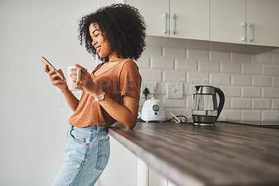 Buy stock photo Shot of a young woman using a smartphone and having coffee in the kitchen at home