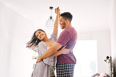Buy stock photo Shot of a happy young couple dancing together in their bedroom at home