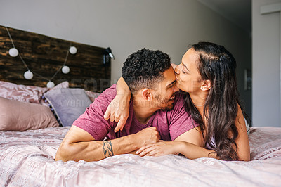 Buy stock photo Shot of an affectionate young couple sharing a romantic moment in the bedroom at home