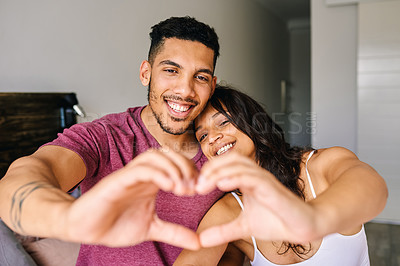 Buy stock photo Shot of a happy young couple making a heart shaped gesture with their hands at home
