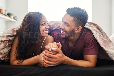 Buy stock photo Shot of a happy young couple relaxing in bed together at home