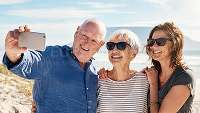 Buy stock photo Shot of a young woman taking selfies with her elderly parents at the beach