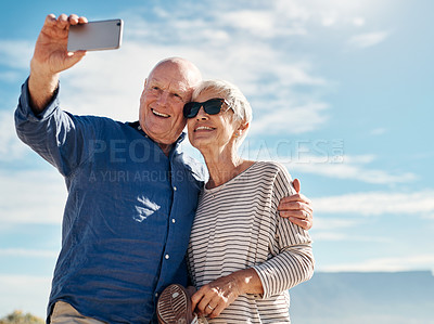 Buy stock photo Shot of a senior couple taking selfies at the beach