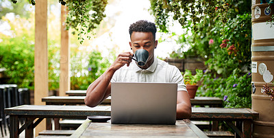 Buy stock photo Shot of a young man using a laptop and having coffee at a restaurant