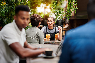 Buy stock photo Shot of two young women chatting and having a drinks at a restaurant