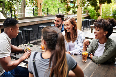 Buy stock photo Shot of a group of young friends having drinks at a restaurant