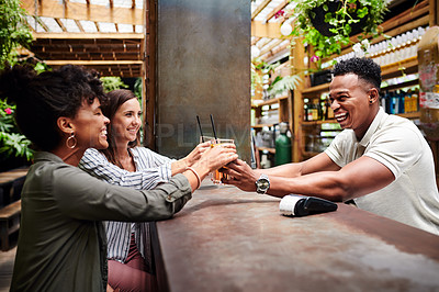 Buy stock photo Shot of a young man serving two young women drinks at a bar