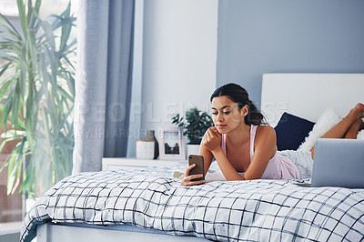 Buy stock photo Cropped shot of an attractive young woman lying on her bed and texting on her cellphone while at home alone