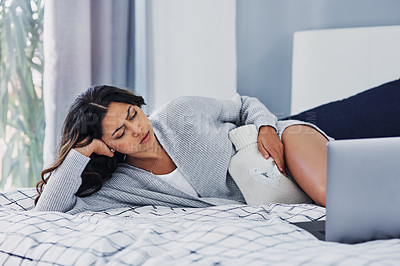 Buy stock photo Cropped shot of an attractive young woman lying on her bed and suffering from period pains while using her laptop