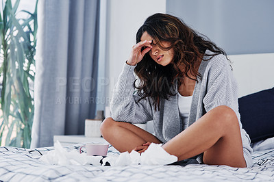 Buy stock photo Full length shot of an attractive young woman suffering from a headache while sitting on her bed alone at home