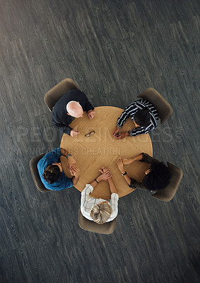 Buy stock photo High angle shot of a group of businesspeople having a meeting around a table in an office