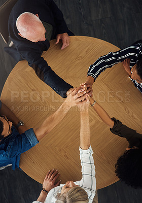 Buy stock photo High angle shot of a group of businesspeople joining their hands together in a huddle around a table in an office