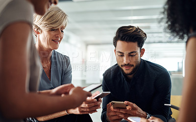 Buy stock photo Cropped shot of a group of businesspeople using their smartphones together in synchronicity at work