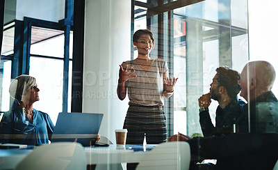 Buy stock photo Shot of an attractive young businesswoman presenting her ideas at a boardroom meeting with colleagues at work