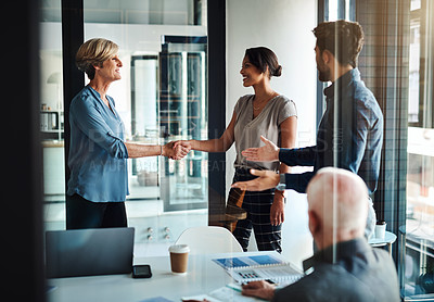 Buy stock photo Shot of two businesswomen shaking hands together during a boardroom meeting at work