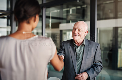 Buy stock photo Shot of a mature businessman shaking hands with a colleague at work