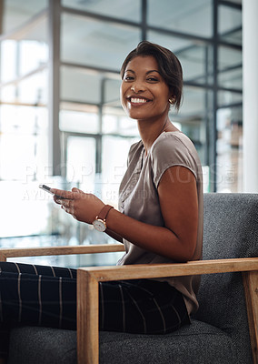 Buy stock photo Portrait of an attractive and confident young businesswoman using her cellphone at work