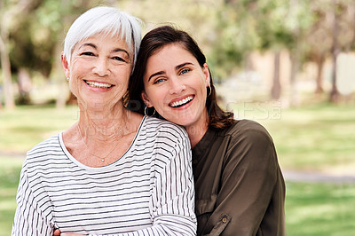 Buy stock photo Shot of a young woman bonding with her elderly mother at the park