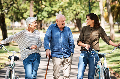 Buy stock photo Shot of a young woman spending the day outdoors with her elderly parents