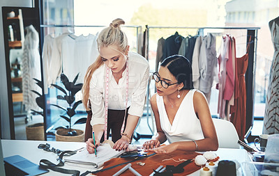 Buy stock photo Shot of two young fashion designers working together in a workshop