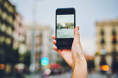 Buy stock photo Cropped shot of an unrecognizable woman standing alone and taking a picture of the city with her cellphone