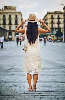 Buy stock photo Rearview shot of an unrecognizable woman standing alone and facing the city during a vacation in Spain