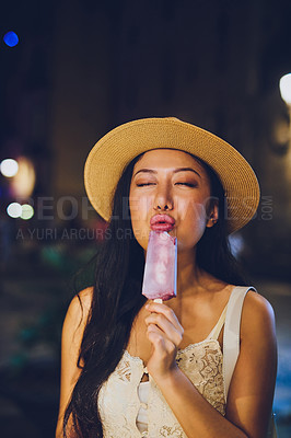 Buy stock photo Cropped shot of an attractive young woman standing alone and holding an ice lolly during late night sightseeing in Spain