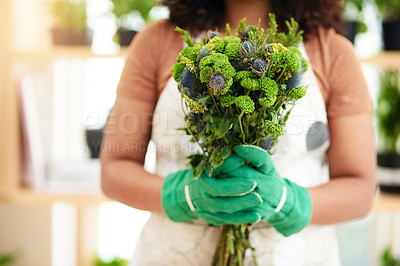 Buy stock photo Cropped shot of an unrecognizable young female botanist holding a bouquet of flowers while working in her florist