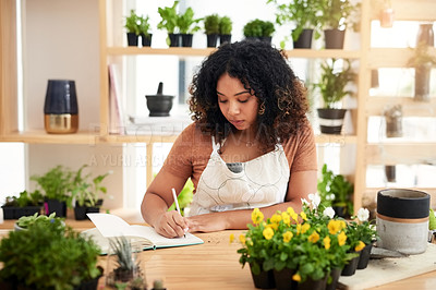 Buy stock photo Cropped shot of an attractive young female botanist making notes while working in her florist