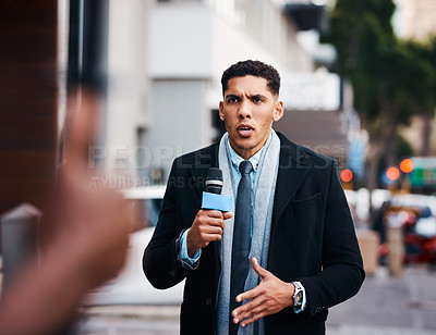 Buy stock photo Shot of a handsome young news reporter covering a story outdoors in the city