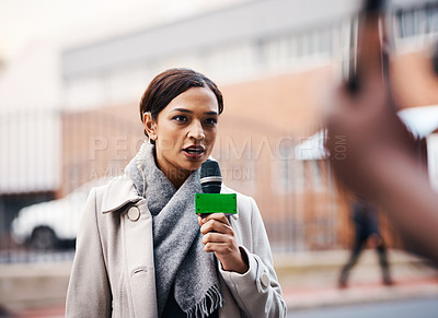Buy stock photo Shot of an attractive young news reporter covering a story outdoors in the city