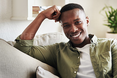Buy stock photo Cropped portrait of a handsome young man smiling while relaxing on his couch at home