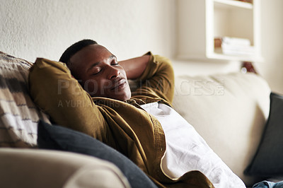 Buy stock photo Cropped shot of a handsome young man sleeping on the couch in his living room at home