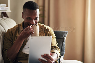 Buy stock photo Cropped shot of a handsome young man drinking coffee while using a digital tablet in his living room at home